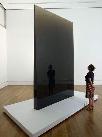 A visitor stands beside De Wain Valentine's monumental sculpture, Gray Column (1975-6)