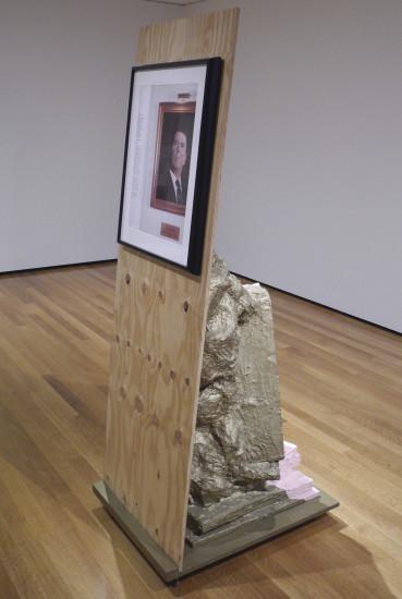Hans Haacke with Sculpture, 2005. Rachel Harrison (American, b. 1966). Wood, chicken wire, polystyrene, cement, acrylic, wheels, and pigmented inkjet print of Oelgemaelde, Hommage à Marcel Broodthaers (1982) by Hans Haacke (German, act. U.S., b. 1936). 190.5 x 61 x 78.7 cm. Courtesy of the artist and Greene Naftali, New York.