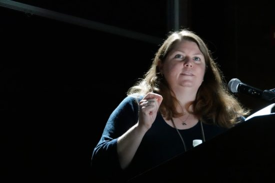 A photograph of Alison Ghilcrest behind a microphone in a dark space
