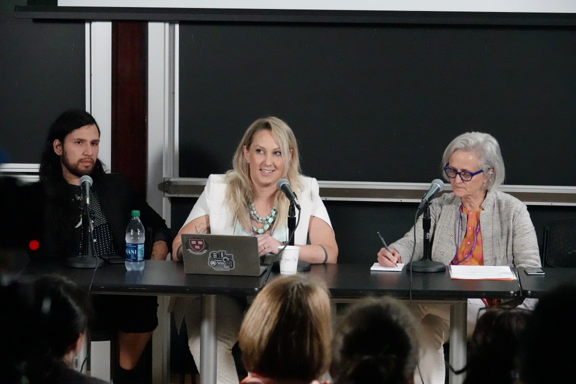 "A photograph of Alfredo Salazar-Caro, Tina Rivers Ryan, and Jill Sterrett sitting at a table in front of an audience at NYU's ""It's About Time!"" Symposium"