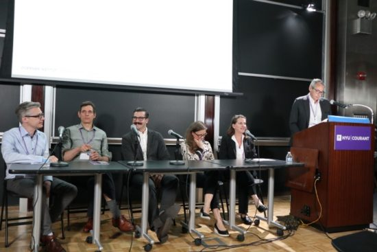 """A photograph of Andreas Weisser, Reinhard Bek, Ben Fino-Radin, Agathe Jarczyk, and Christine Frohnert sitting at a table with microphones and Paul Messier standing behind a podium at the NYU """"It's About Time!"""" Symposium"""