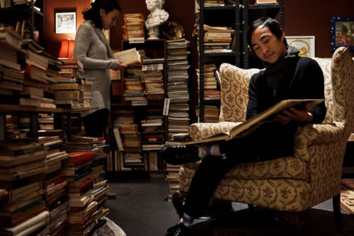 A man sits in a bookstore where the shelves are covered floor to ceiling with books, reading an oversize book.