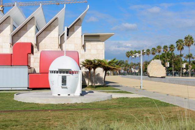 "NuMu. A white egg-shaped pod sits outside LACMA next to Michael Heizer's ""Levitated Mass"""