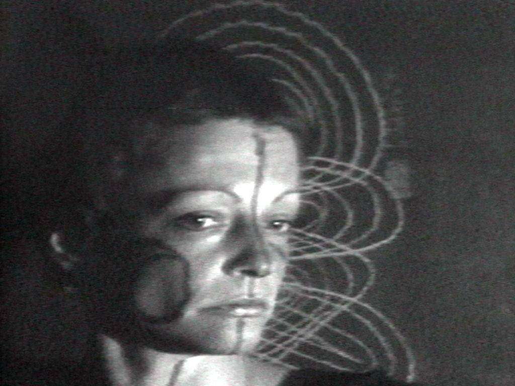 A grainy black and white film still showing a woman's face, painted with symbols, in front of a series of interlocking lines