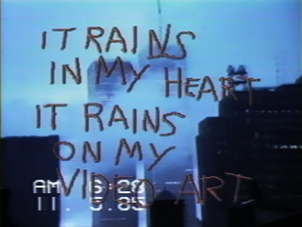 """A film still showing the World Trade Towers, time stamped AM 6:28, 11.5.85, overlaid with the words """"IT RAINS IN MY HEART IT RAINS ON MY VIDEO ART"""""""