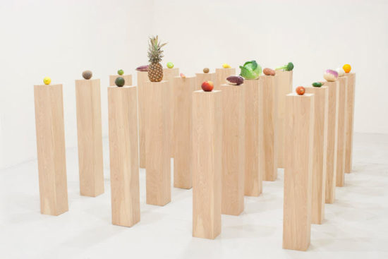Various fresh fruits and vegetables sit atop 40 narrow light wood pedestals of equal height