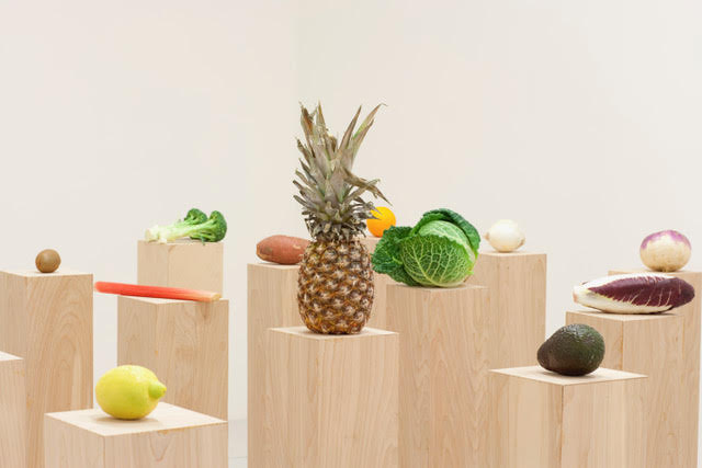 Pineapple, cabbage, lemon and other produce sit on top of natural wood plinths, evenly spaced in a white gallery
