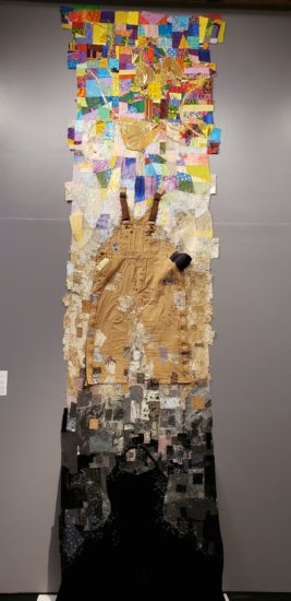 A quilt stands over 17 feet tall, transitioning from a disorganized blur of black fabrics, to brown fabrics (including a pair of overalls the interview subject associates with her lost lover), and finally to patterns of brightly colored clothes and a golden bikini