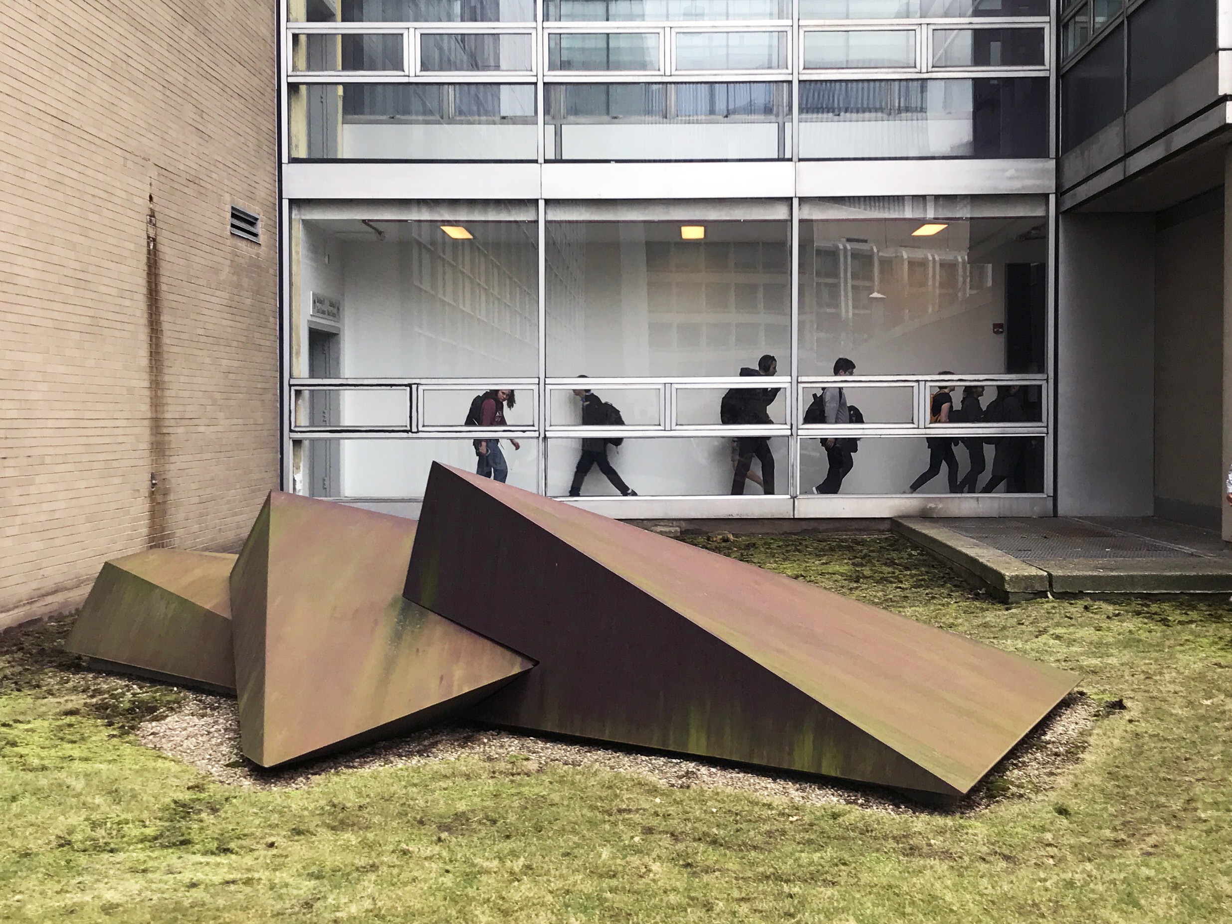 Students are visible walking through the hallway behind Beverly Pepper's Trinity, 1971, which sits on the lawn between MIT Buildings 16 and 26.