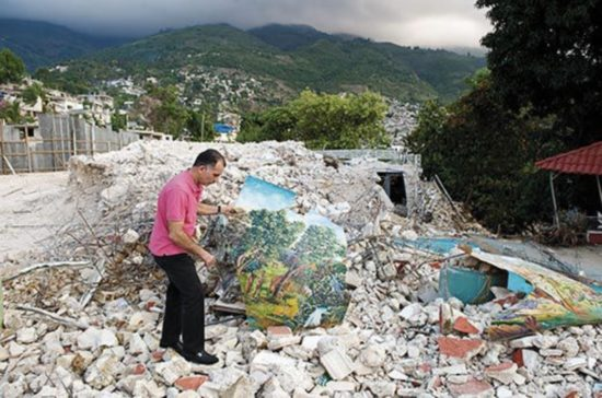 A man stands amidst the wreckage of a museum after an earthquake, pulling paintings out of the rubble