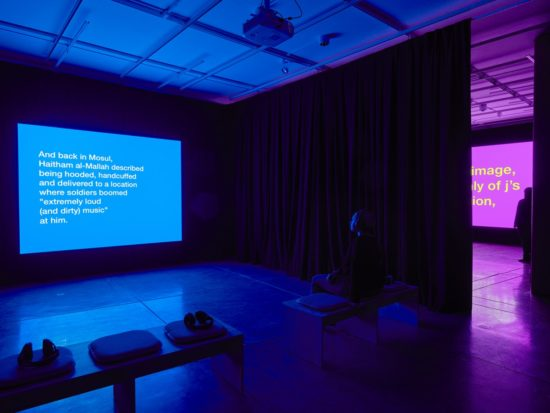 A bright blue screen covered in white text illuminates a dark room. One person sits in a chair looking at the screen,