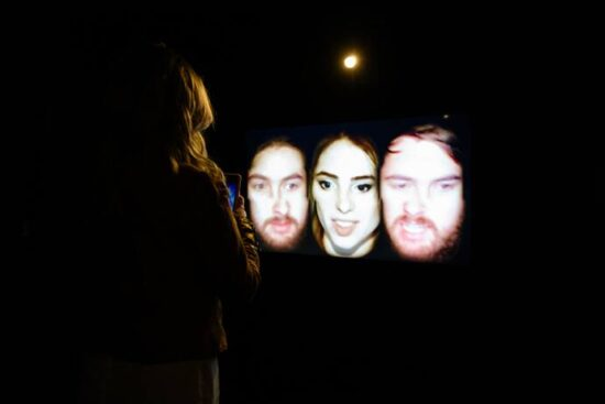 Three faces projected on a black screen